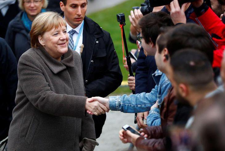 9日、記念式典で市民らと握手するドイツのメルケル首相=ベルリン(ロイター=共同)