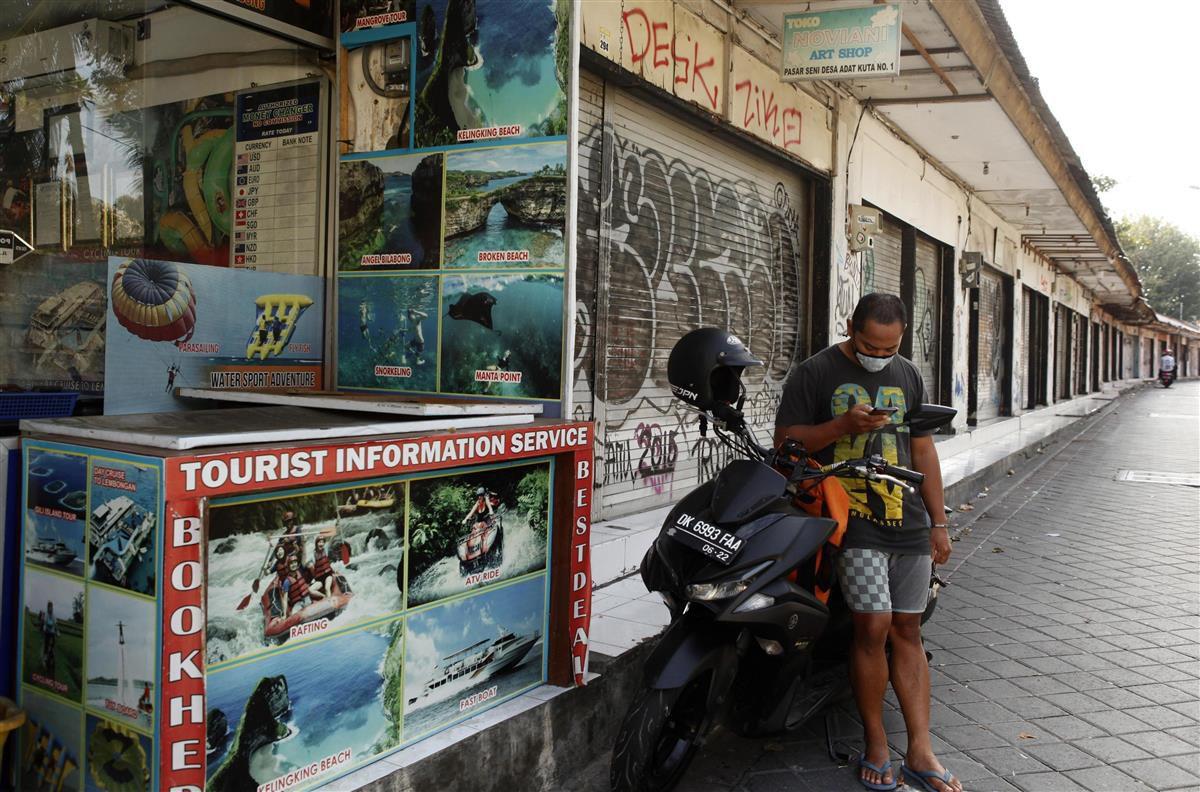 インドネシア・バリ島で携帯電話をチェックする男性=7月27日(AP=共同)