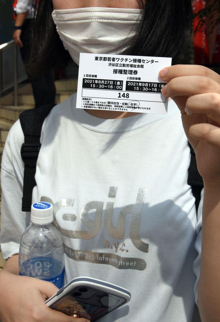 朝6時から並んだという20代の女性は、整理券番号148。午後3時半からの接種となる=27日午前9時19分、東京都渋谷区(酒巻俊介撮影)