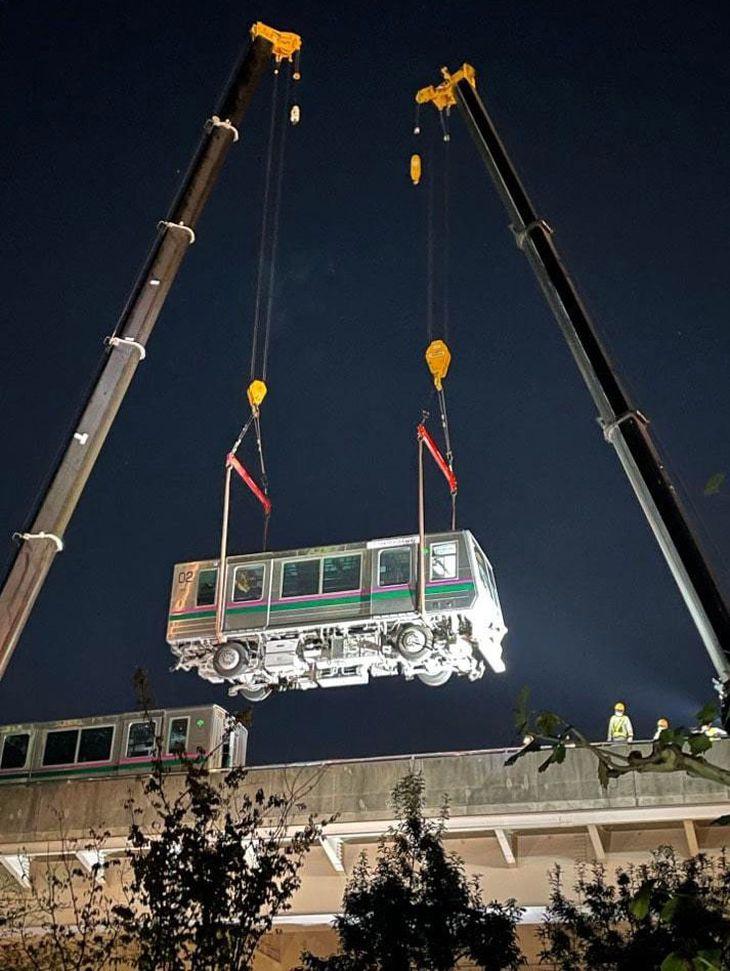 高架上の脱線現場からクレーンにつり上げられ、撤去される新交通システム「日暮里・舎人ライナー」の車両=8日午後8時21分、東京都足立区