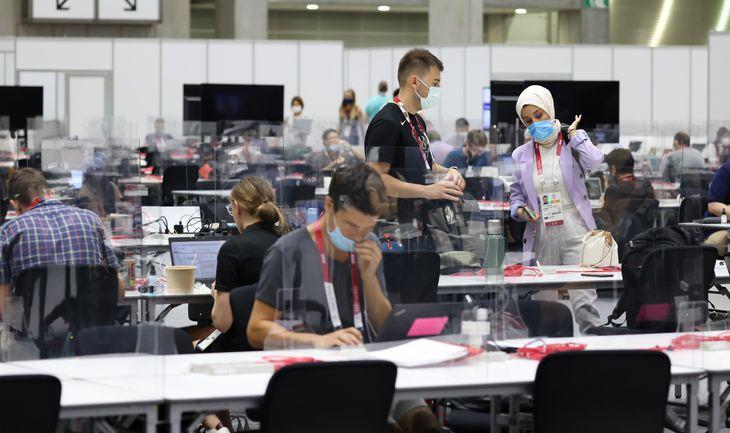 東京五輪のメインプレスセンター(MPC)の共同スペースで作業をする記者やカメラマン=19日、東京都江東区(川口良介撮影)