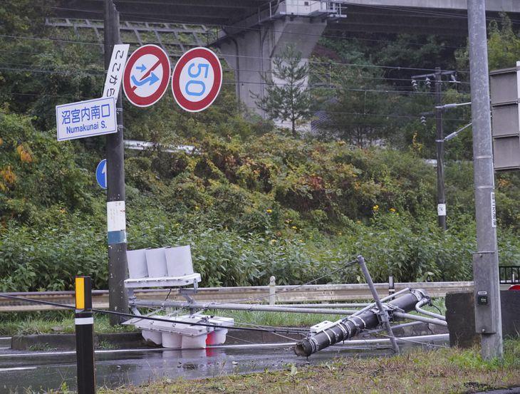 地震の影響で道路に倒れた信号機と傾いた道路標識=6日午前6時3分、岩手県岩手町