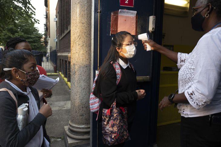 13日、米ニューヨーク市の小学校に登校し、体温測定をする少女(AP=共同)