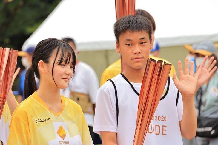 聖火イベントで手を振る杉之原みずきさん(左)と双子の兄、一樹さん=8月(千里さん提供)