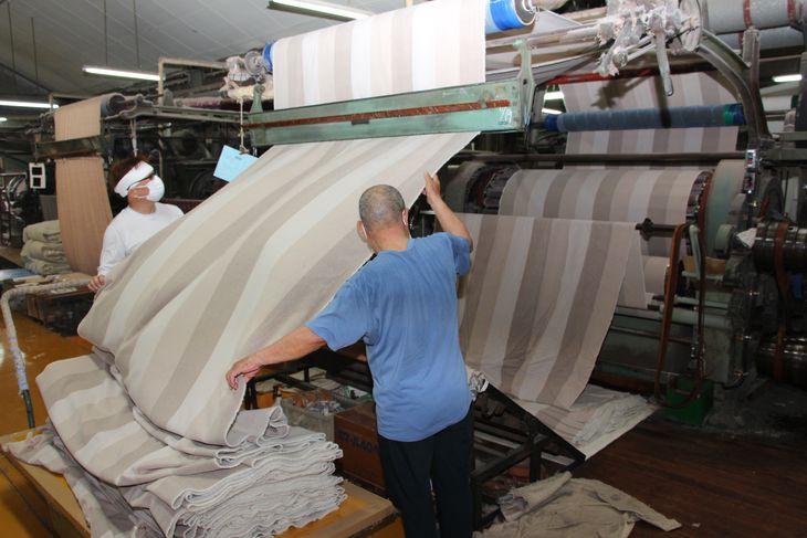 起毛機にかけられた織毛布。何回かけて、どんな風合いに仕上げるかは熟練工の判断だ=大阪府泉大津市の今新毛織