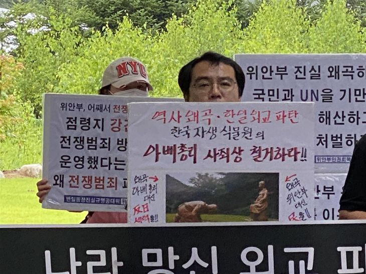 3日、慰安婦像にひざまずき謝罪する安倍晋三首相を模した像が設置された韓国自生植物園で、像の撤去を求める市民団体(参加者提供)