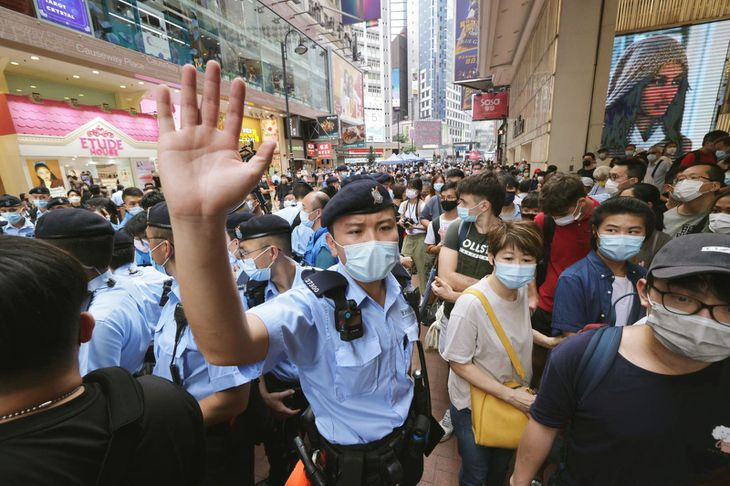 7月1日、香港の繁華街コーズウェイベイ(銅鑼湾)で、デモを取り締まる警官隊(共同)