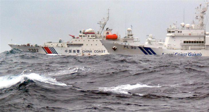 日本漁船に接近しようとする中国公船(左)と阻止する海保の巡視船=26日午後、尖閣諸島周辺(仲間均氏提供)