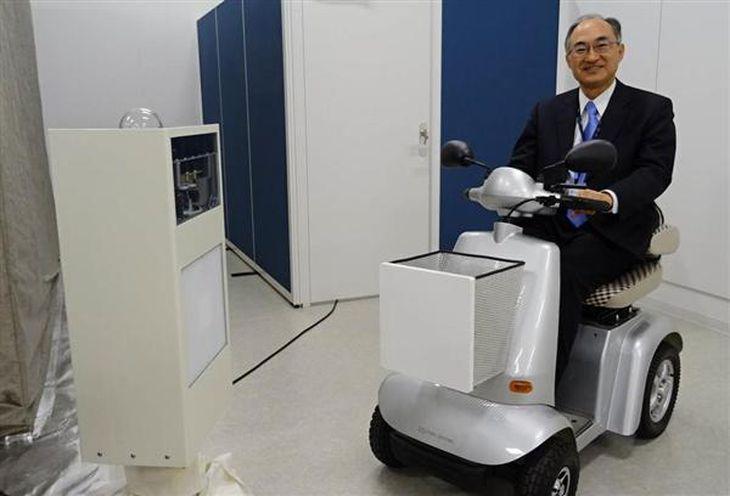 京都大が三菱重工業と共同開発した小型電動車両「シニアカー」(右)。ワイヤレス給電技術を使った送電機器(左)の近くにいるだけで、車両のバッテリーに電気を充電できる=22日午後2時40分ごろ、京都市左京区の京都大(西川博明撮影)
