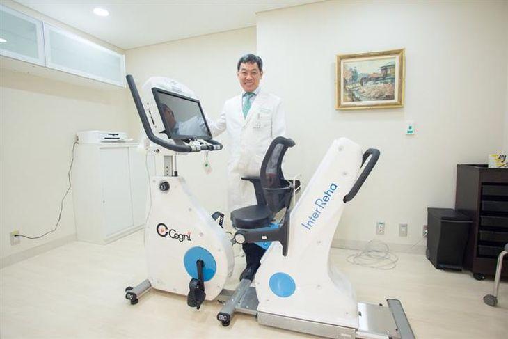 新宿白澤記念クリニックで運動しながら認知機能を検査できる「コグニバイク」を説明する白澤先生