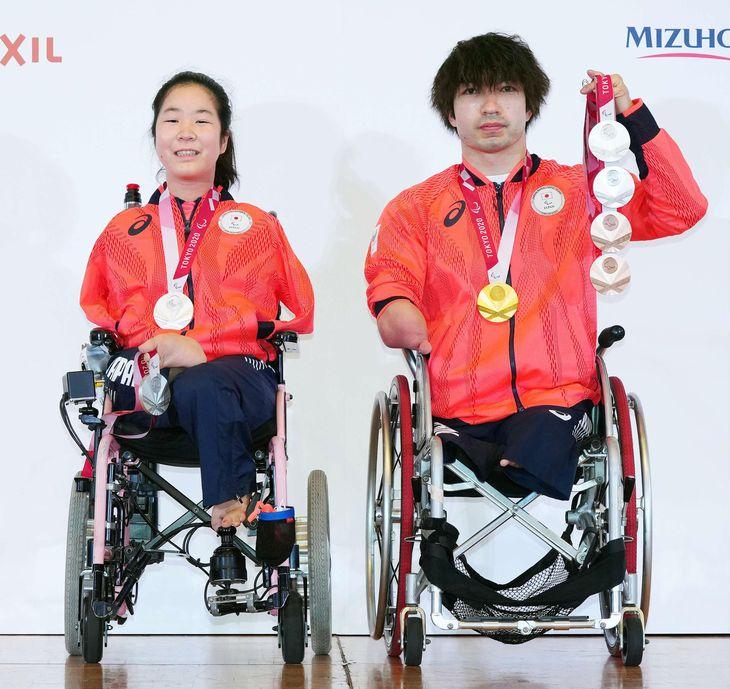 記者会見でメダルを披露する山田美幸(左)と鈴木孝幸=3日、東京都内(代表撮影)