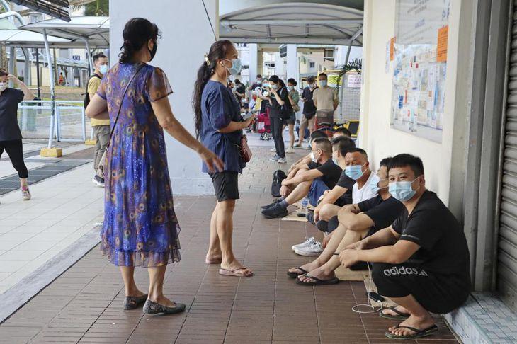 中国製の新型コロナウイルスワクチンの接種を受けられる診療所前で早朝から並ぶ人々=シンガポール(共同)