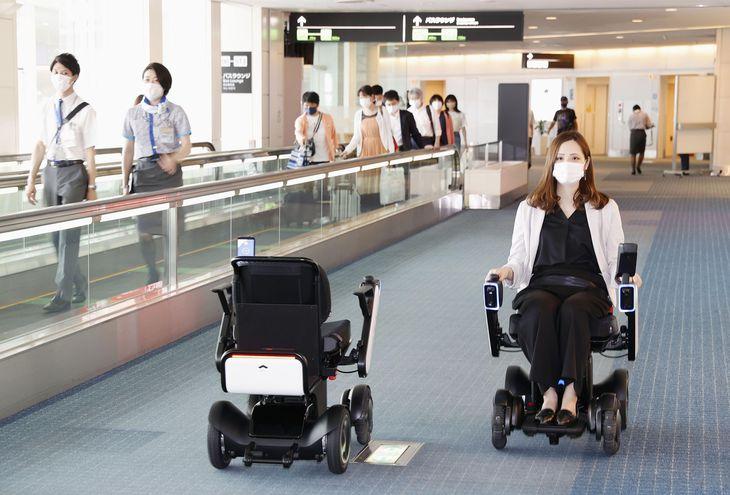 自動運転車いすで移動する担当者。左は無人で待機場所に戻る車体=22日午後、羽田空港第2ターミナル