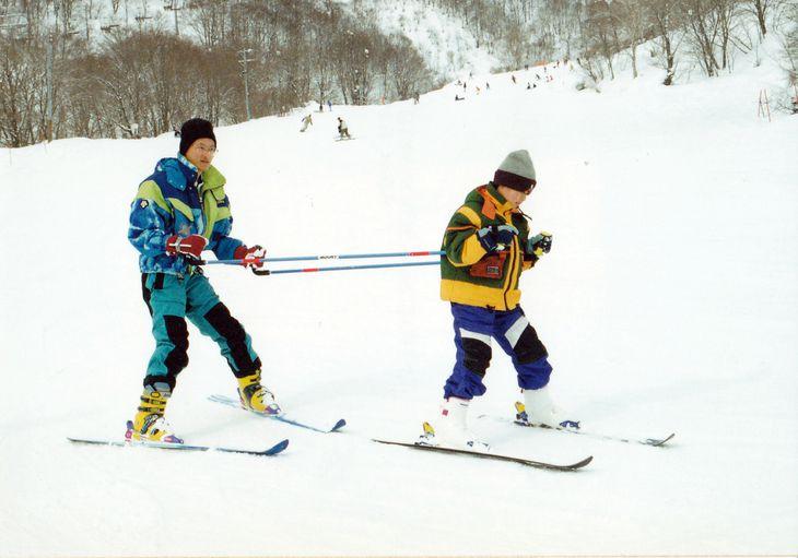 補助具を使ってスキーを楽しむ木村敬一(右)=平成13年、岐阜県(木村稔さん提供)