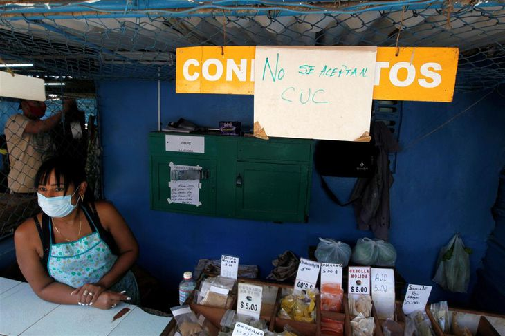 二重通貨制廃止に備えて店に「兌換ペソ(CUC)は使えません」と掲げてスパイスを売る女性=2020年12月29日、ハバナの市場(ロイター)