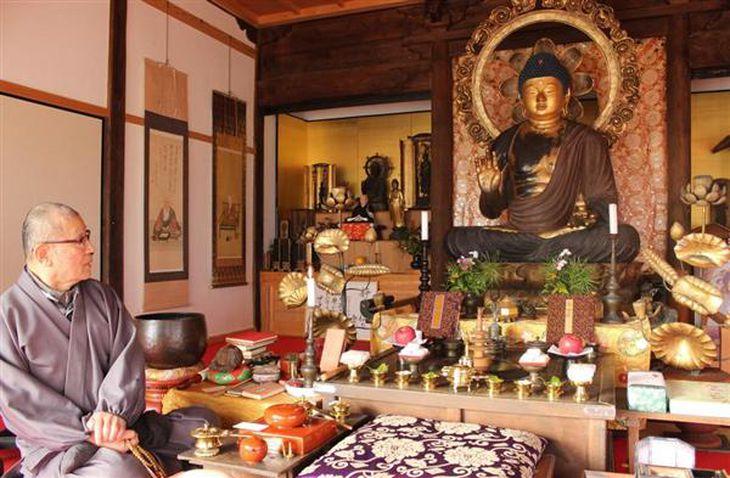 本尊の弥勒如来坐像を見つめる伊藤教純住職。「後世へ守り続けたい」と話した=奈良県大和高田市