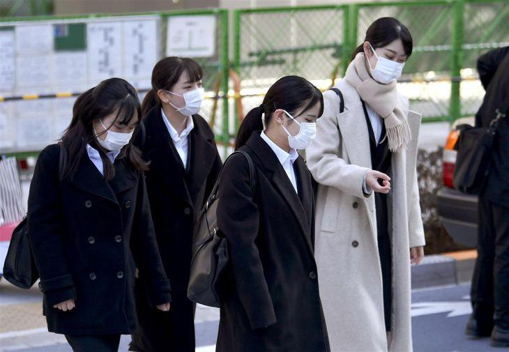 マスク姿で合同会社説明会の会場に向かう就職活動の学生ら=3月1日、東京都港区