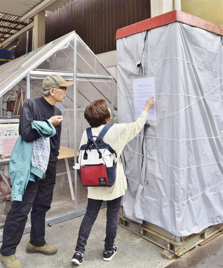 水が抜かれ、カバーがかけられた「金魚電話ボックス」=奈良県大和郡山市