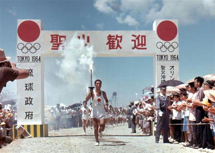 那覇飛行場に到着後、歓迎式典会場に向かう聖火リレー。看板には「琉球政府」の文字があった(1964年9月7日、現在の那覇市)