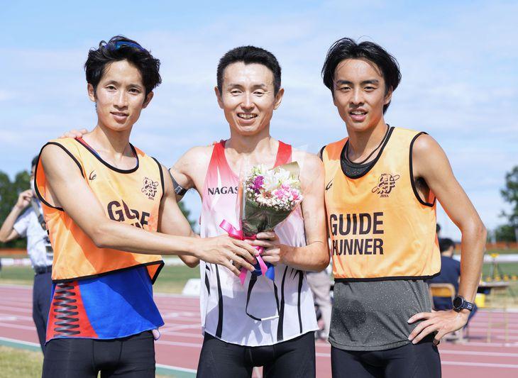 今年7月に行われた競技会で5000メートルを1位でゴールし、ポーズをとる和田伸也選手(中央)と長谷部匠さん(右)=7月10日、北海道・網走市営陸上競技場