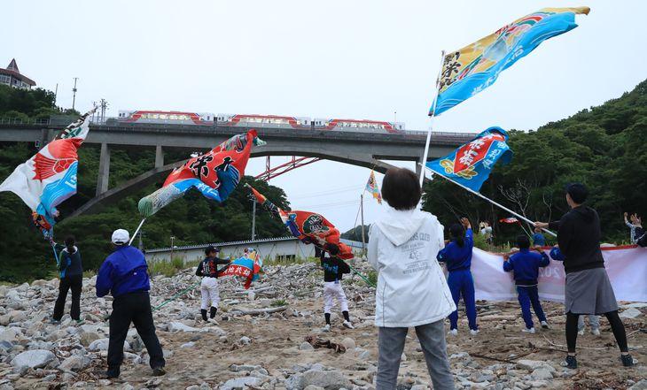 三陸鉄道リアス線の大沢橋梁を通る聖火をの乗せた列車。地元の人たちらは大漁旗を振って見送った =16日午後、岩手県普代村(佐藤徳昭撮影)