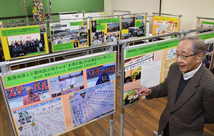 企画展の会場で神戸と全国との絆について説明する杉本和夫さん=神戸市長田区
