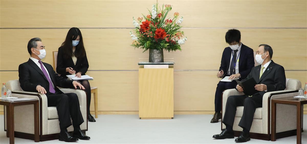 会談に臨む中国の王毅国務委員兼外相(左)と菅義偉首相=25日午後、首相官邸(春名中撮影)