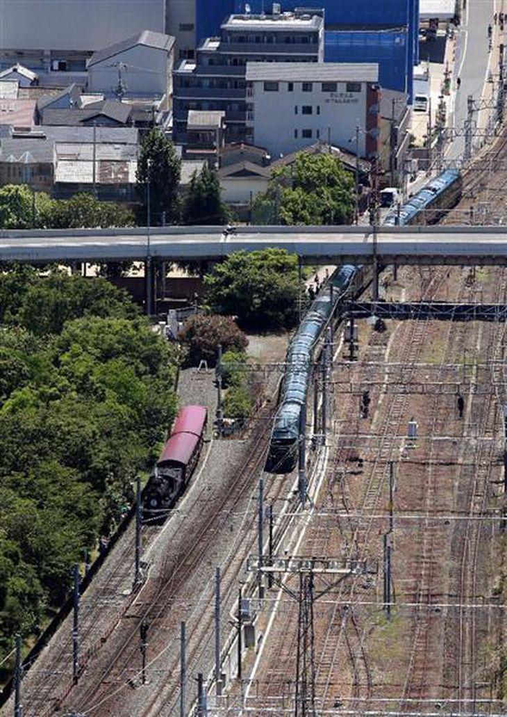 京都駅を出発した「トワイライトエクスプレス瑞風」。写真左は京都鉄道博物館の蒸気機関車「SLスチーム号」 =17日午前10時56分、京都市(本社ヘリから、志儀駒貴撮影)