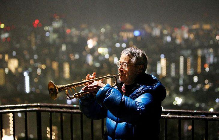 昨年の「早朝追悼のつどい」でトランペットを響かせる松平晃さん。つどいは今年で最後となる=昨年1月17日午前6時22分、神戸市中央区
