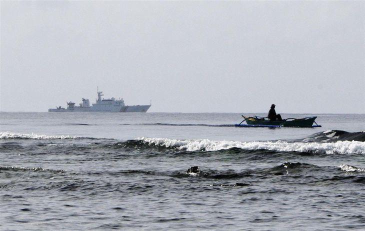 南シナ海スカボロー礁周辺で停泊する中国海警局の艦船(左)と、操業するフィリピン人漁師の船=2016年12月(共同)