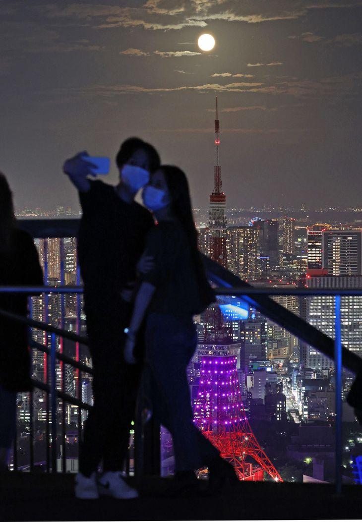 【中秋の名月2021】中秋の名月の満月と東京タワー(中央)。六本木ヒルズスカイデッキでは写真撮影する人の姿もみられた=21日夜、東京都港区(佐藤徳昭撮影)