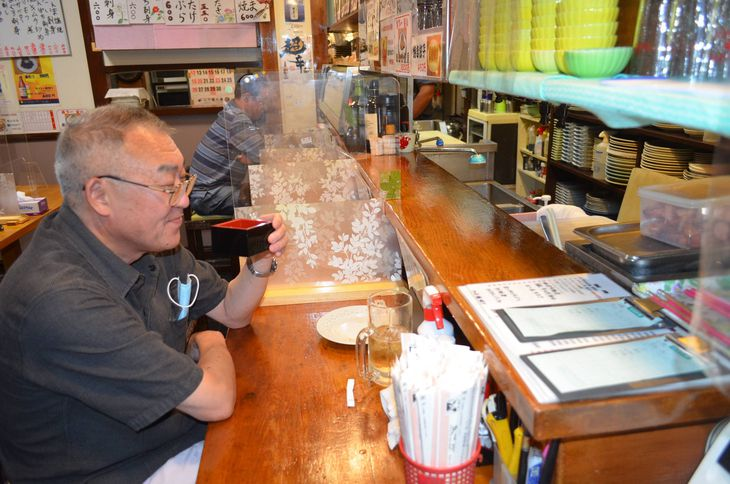 「大衆割烹友四郎」の営業再開直後に来店し、日本酒を楽しむ常連客=13日、甲府市(平尾孝撮影)
