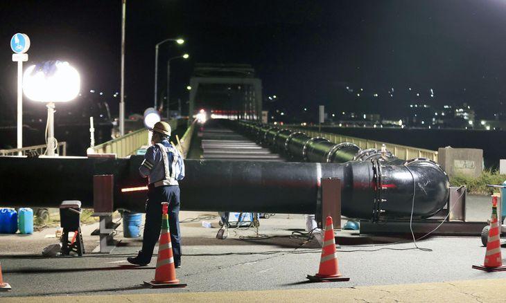 一部が崩落した「水管橋」に並行する県道の橋に設置された仮の管=8日夜、和歌山市