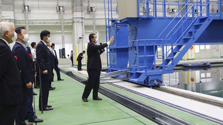防衛装備庁の水中無人機試験施設を視察する岸防衛相(左手前から3人目)=5日、山口県岩国市