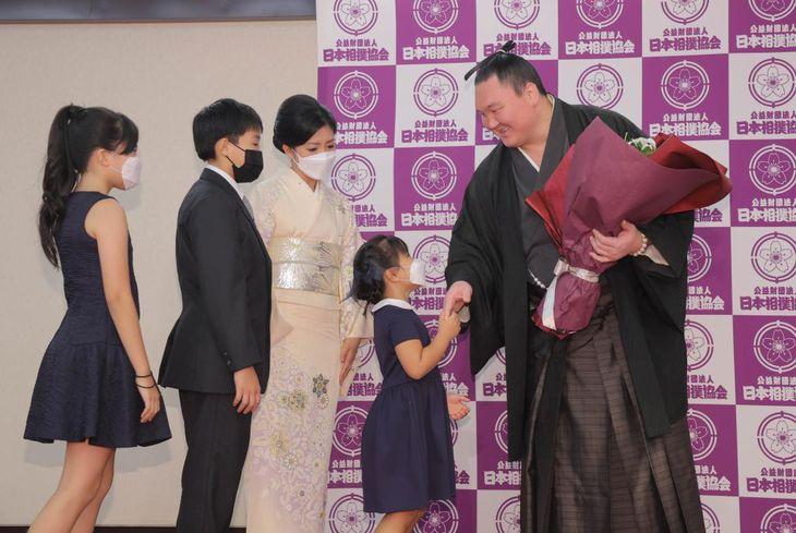 引退会見で紗代子夫人(中央)ら家族から花束を受け取る元横綱白鵬(代表撮影)