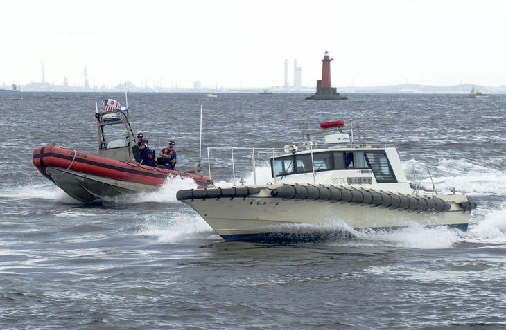合同訓練で、不審船に見立てた監視取締艇を停船させる米国沿岸警備隊のゴムボート(左)=3日午後、神奈川県横須賀市の横須賀港内