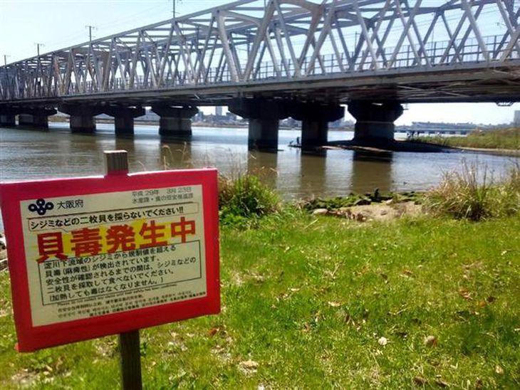 淀川の河川敷に立てられている、貝毒への注意を促す看板=大阪市淀川区