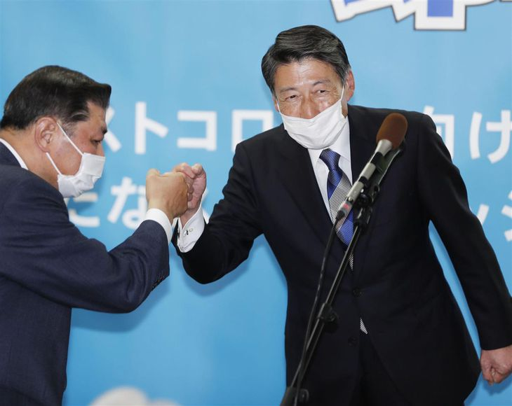 福岡県知事選で初当選を決め、支援者とグータッチを交わす服部誠太郎氏(右)=11日夜、福岡市