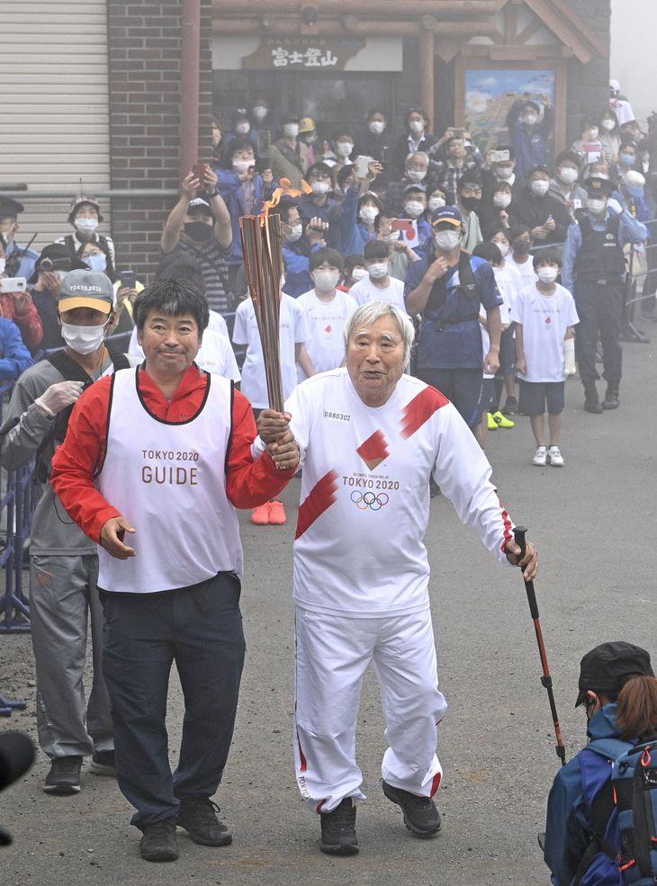 山梨県側の富士山5合目で聖火ランナーを務める冒険家の三浦雄一郎さん。左は次男の豪太さん=27日午前