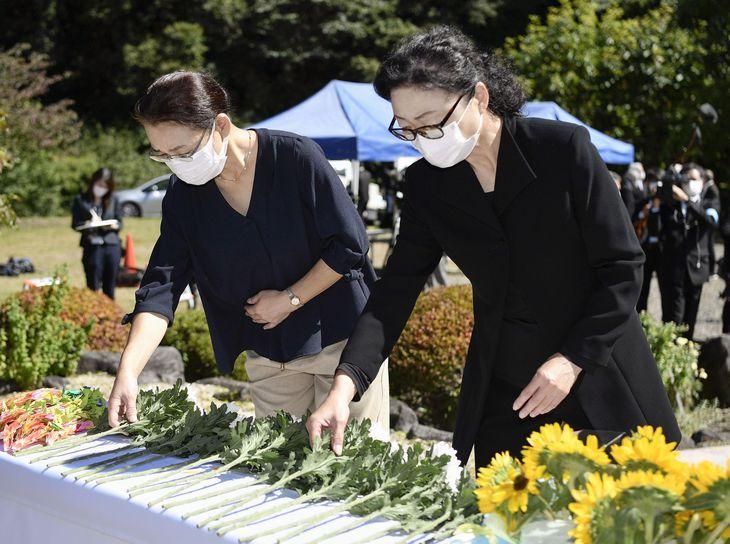 御嶽山の噴火から7年となり、献花する伊藤ひろ美さん(左)とシャーロック英子さん=27日午後、長野県王滝村