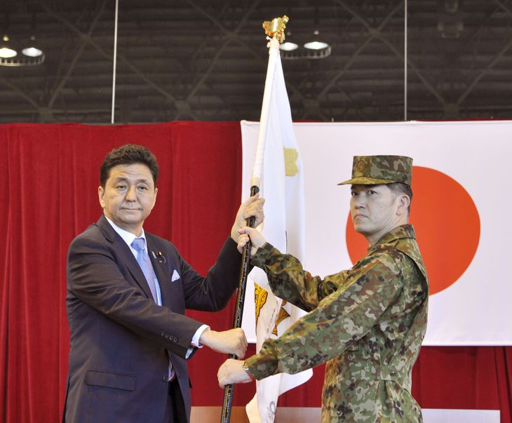 東京五輪・パラリンピックに支援団として派遣される自衛官(右)に団旗を手渡す岸信夫防衛相=18日午前、陸上自衛隊朝霞駐屯地