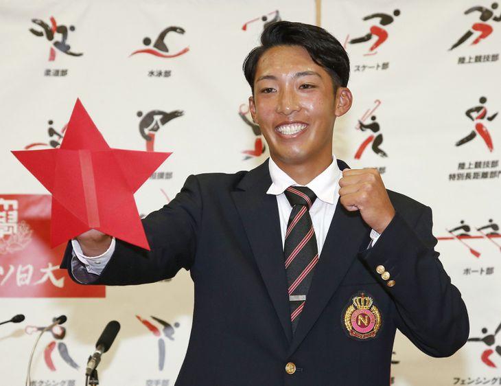 巨人から3位指名を受け、ガッツポーズをとる日大の赤星優志投手=11日、千葉県習志野市