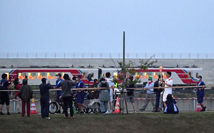 三陸鉄道と並走する聖火ランナー=16日午後、岩手県野田村(宮崎瑞穂撮影)