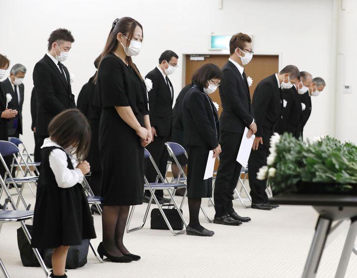 宮城県丸森町で開かれた台風19号の犠牲者追悼式で、黙とうする遺族ら=12日午前