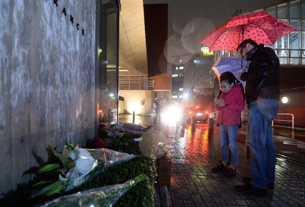 フランス大使館に花を供えに来た外国人の親子=14日午後、東京都港区(鴨川一也撮影)