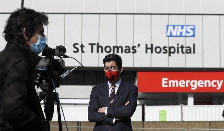 7日、ジョンソン英首相が入院するロンドンの病院前で、マスクを着用して待機する報道関係者(AP)