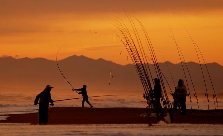北海道・知床半島を望む網走市の海岸で、朝日を浴びながらサケを狙う釣り人たち=7日早朝