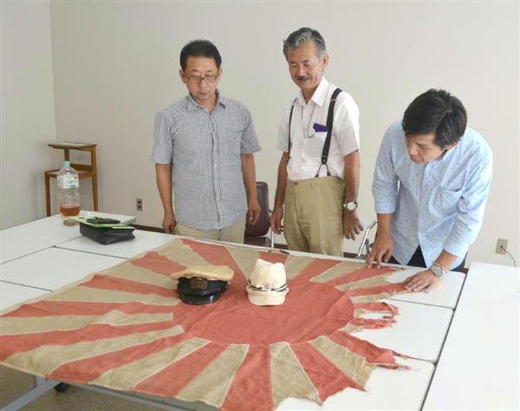 戦時中に使われたとみられる旭日旗を見つめる青年部の発起人の3人=神戸市中央区