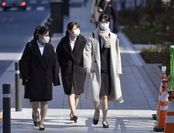 新型コロナウイルスの感染拡大を受け、マスク姿で合同会社説明会の会場に向かう就職活動の学生ら=3月1日午前、東京都港区