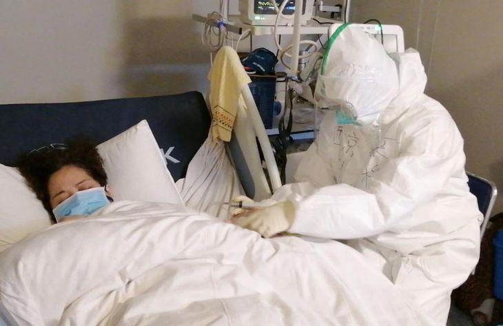 中国・武漢の病院で、防護服姿で新型肺炎の患者の手当てをする看護師=1月29日(新華社=共同)